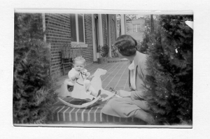 Baby on front porch on rocking horse